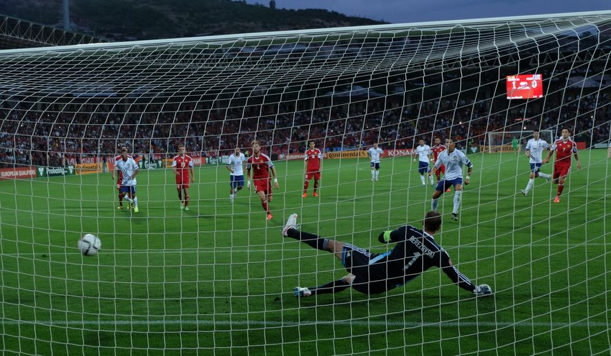 Portugal's Cristiano Ronaldo, right # 7, scores the first goal in Armenia's gate during the Euro 2016 Group I qualifying match between Armenia and Portugal in Yerevan, Armenia, Saturday, June 13, 2015. (AP Photo/ Hrant Khachatryan, PAN Photo)