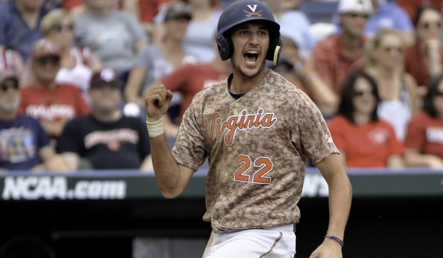 Virginia's Daniel Pinero celebrates after scoring on an RBI double by Kenny Towns in the eighth inning of an NCAA College World Series baseball game against Arkansas at TD Ameritrade Park in Omaha, Neb., Saturday, June 13, 2015. (AP Photo/Ted Kirk)
