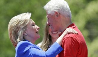 Democratic presidential candidate, former Secretary of State Hillary Rodham Clinton, left, hugs her husband former President Bill Clinton after speaking to supporters Saturday, June 13, 2015, on Roosevelt Island in New York.  (AP Photo/Frank Franklin II)