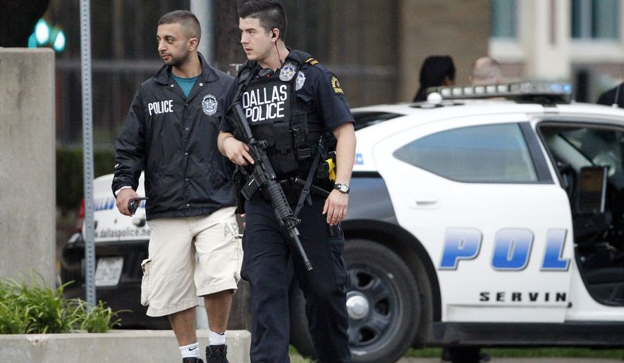 Dallas police officers walk down Belleview Street one block away from police headquarters searching the area Saturday June 13, 2015, in Dallas.   A police sniper shot a cornered suspect in an overnight attack on the Dallas Police Department's headquarters, and authorities were checking Saturday to see if he was alive or dead. (AP Photo/Tony Gutierrez)
