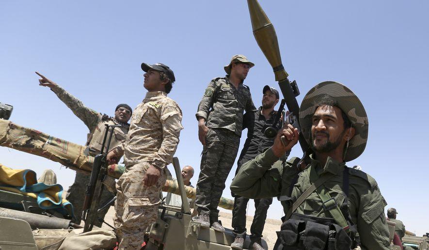 Fighters from the Shiite Badr Brigades militia patrol at the front line, in Kessarrat, (70 kilometers) northwest of Baghdad, Iraq, June 12, 2015. (Associated Press) ** FILE **