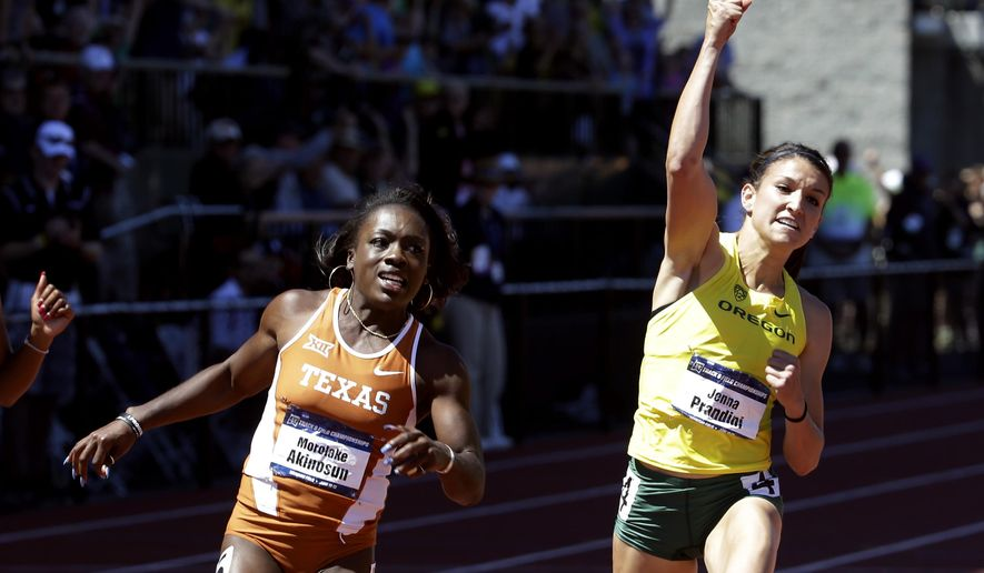 Oregon's Jenna Prandini, right, celebrates winning the women's 100 meters ahead of Texas' Morolake Akinosun during the NCAA track and field championships in Eugene, Ore., Saturday, June 13, 2015. Akinosun finished second. (AP Photo/Don Ryan)