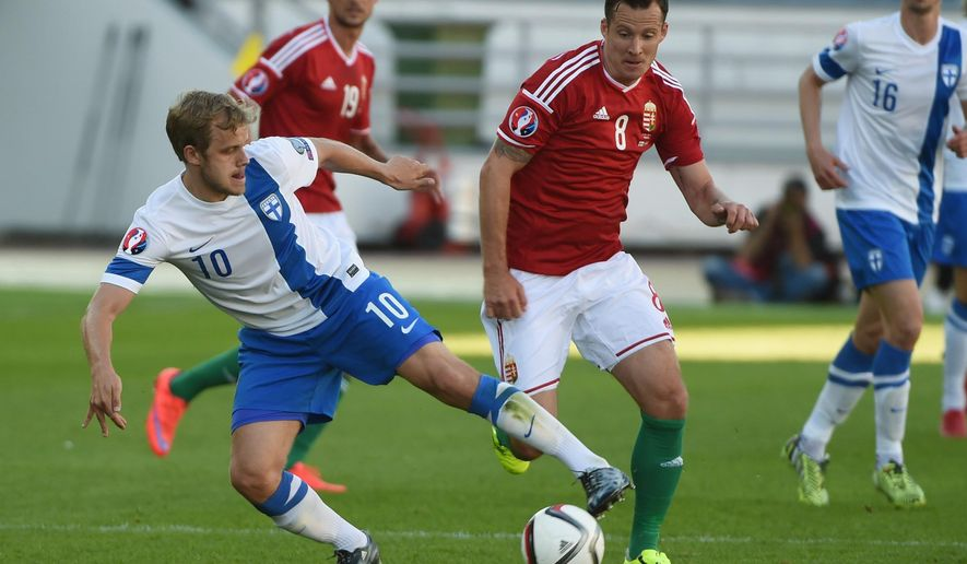 Teemu Pukki of Finland, left, and Daniel Tozser of Hungary in action during their UEFA EURO 2016 phase 1 qualification match between Finland and Hungary at the Helsinki Olympic Stadium on Saturday June 13, 2015.  (Jussi Nukari/Lehtikuva via AP) FINLAND OUT - NO SALES