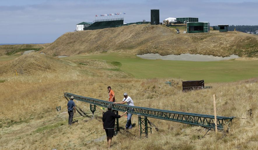 Technicians adjust a long video camera slider rail Thursday, June 11, 2015, on the 18th hole at Chambers Bay golf course in University Place, Wash. In its bid to take over the U.S. Open from NBC, Fox promised innovative coverage and will feature new graphics and cameras as the network broadcasts the tournament for the first time next week. (AP Photo/Ted S. Warren)