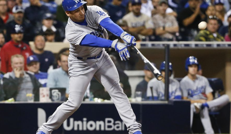 Los Angeles Dodgers' Alex Guerrero reaches out to slap a bloop single to center field and drive in Andre Ethier against the San Diego Padres in the eighth inning of a baseball game Friday, June 12, 2015, in San Diego.  (AP Photo/Lenny Ignelzi)