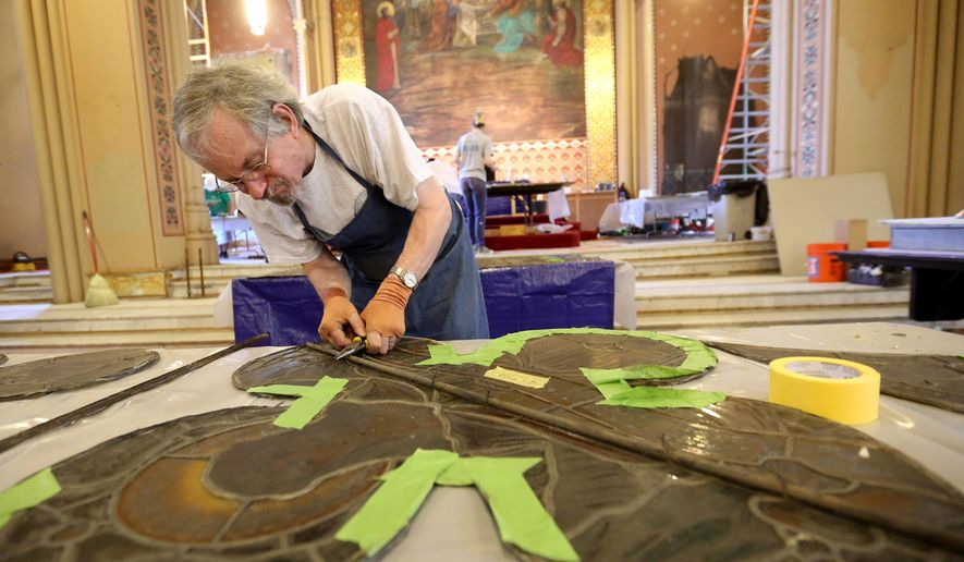 FOR USE SATURDAY JUNE 13 OR THEREAFTER- John Clark, with Restoric LLC in Chicago, works with a stained-glass panel  Wednesday, June 10, 2015, at Steeple Square in Dubuque, Iowa. (Jessica Reilly/Telegraph Herald via AP)