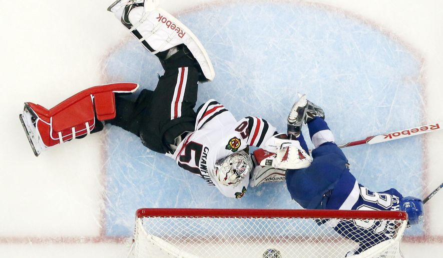 Tampa Bay Lightning right wing Nikita Kucherov (86) hits the goal post as he collides with Chicago Blackhawks goalie Corey Crawford (50) during the first period of Game 5 of the NHL hockey Stanley Cup Final, Saturday, June 13, 2015, in Tampa, Fla. (AP Photo/Chris O'Meara)