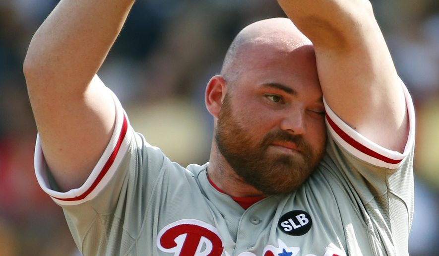Philadelphia Phillies starting pitcher Sean O'Sullivan wipes his head on the mound between pitches in the first inning of a baseball game against the Pittsburgh Pirates in Pittsburgh, Saturday, June 13, 2015. (AP Photo/Gene J. Puskar)