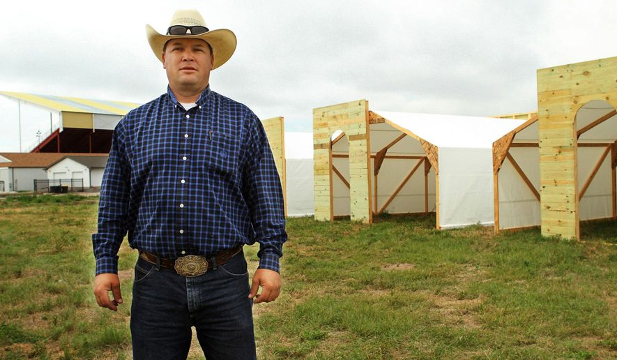 ADVANCE FOR SUNDAY JUNE 14 - In this June 5, 2015 photo, Dusty Barner stands in front of the buildings in the Wild West Town that he, his friends and family have worked on for the past few months in preparation for NEBRASKAland Days in North Platte, Neb. Barner was asked in February or March by Kelly Vap, a NEBRASKAland Days board member, if he had any ideas for an attraction during the rodeo.He developed Wild West Town. The town will be open each day before the Buffalo Bill Rodeo, June 17-20.  (Liz McCue/The Telegraph via AP)
