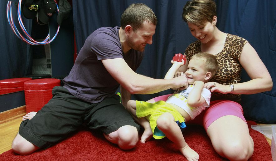 ADVANCE FOR SUNDAY JUNE 14 - In this June 4, 2015 photo, Mike Decker, left, and Brienna Decker, right, tickle their son 3 year old Garrett, center, as they play in his room in Cedar Falls, Iowa.  The Legislature's failure to expand Iowa's medical marijuana law has some parents of sick children looking to Minnesota. Area lawmakers who worked to pass the proposed legislation suggested some Iowans may relocate to nearby states to access medicinal marijuana. Medical marijuana will be legal in limited form in Minnesota beginning July 1. (Tiffany Rushing/The Courier via AP)