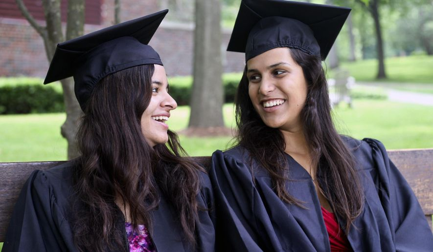 Rani Noor, 22, left, and Indigo McCollum, 21, right, pose at Kalamazoo College Friday, June 12, 2015 in Kalamazoo, Mich. Rani Noor and Indigo McCollum grew up as classmates in Thailand before one family packed up and left the country. Years later, they were reunited at Kalamazoo College. Now they're graduating together. (Daytona Niles/Kalamazoo Gazette-MLive Media Group via AP) ALL LOCAL TELEVISION OUT; LOCAL TELEVISION INTERNET OUT