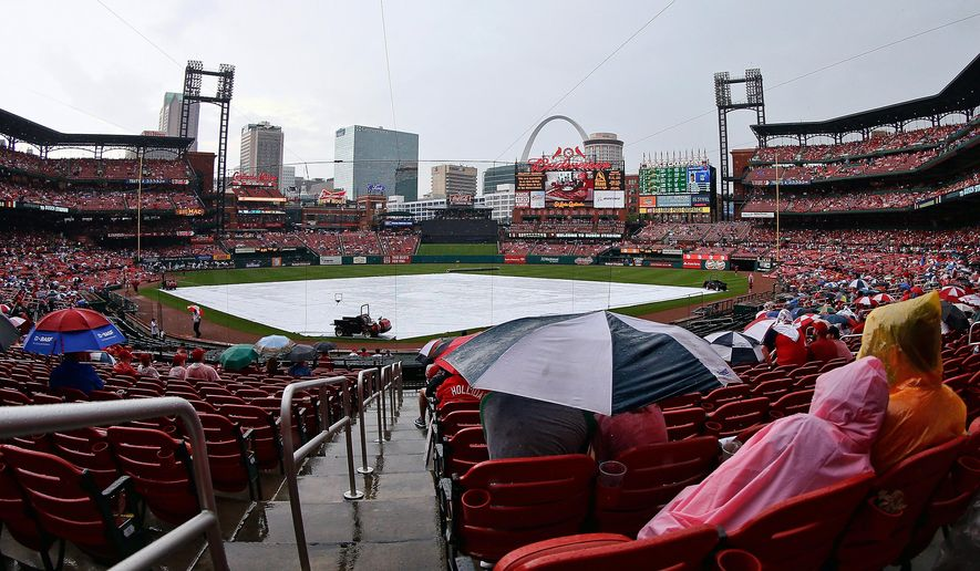 Fans wait out a rain delay before a baseball game between the St. Louis Cardinals and the Kansas City Royals at Busch Stadium, Sunday, June 14, 2015, in St. Louis. (AP Photo/Scott Kane)