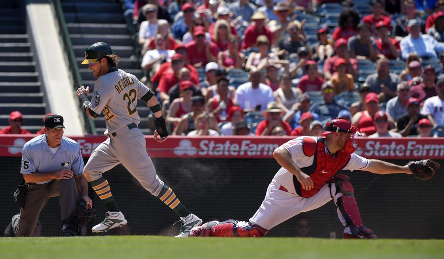 Oakland Athletics' Josh Reddick, center, scores on a ball hit by Brett Lawrie as Los Angeles Angels catcher Chris Iannetta, right, takes a late throw and home plate umpire Angel Hernandez watches during the seventh inning of a baseball game, Sunday, June 14, 2015, in Anaheim, Calif. The Athletics won 8-1. (AP Photo/Mark J. Terrill)