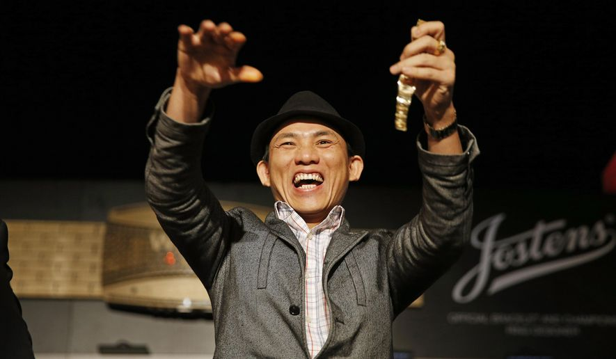 Christian Pham celebrates during a bracelet ceremony after he won the World Series of Poker No-Limit Deuce-to-Seven Lowball Draw tournament Friday, June 12, 2015, in Las Vegas. Pham accidentally entered the No-Limit Deuce-to-Seven Lowball Draw tournament while trying to register for another. (AP Photo/John Locher)