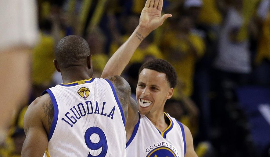 Golden State Warriors guard Stephen Curry (30) celebrates with forward Andre Iguodala (9) during the second half of Game 5 of basketball's NBA Finals against the Cleveland Cavaliers in Oakland, Calif., Sunday, June 14, 2015. (AP Photo/Ben Margot)
