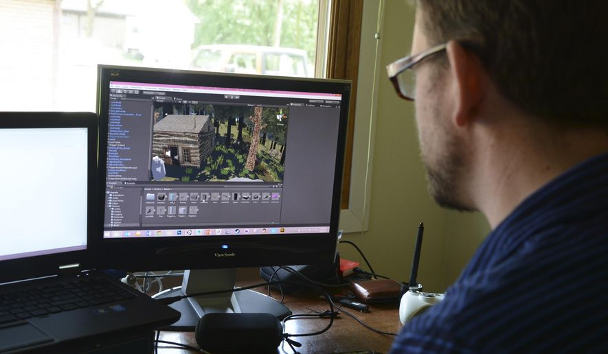 Dave Beck designs the historic Palmer-Epard Cabin on his computer at the Homestead National Monument on June 4, 2015 in Beatrice, Neb.  Beck is a practicing 3D digital and new media artist, living in Wisconsin. He's the current chair of the Department of Design at the University of Wisconsin-Stout, where he teaches 3D art and game design.  (Scott Koperski/Beatrice Daily Sun via AP)
