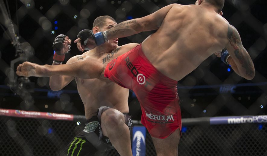 United States' Cain Velasquez, left, battles against Brazil's Fabricio Werdum during a men's heavyweight title UFC 188 mixed arts bout in Mexico City, Saturday, June  13, 2015. Werdum won the fight by submission. (AP Photo/Christian Palma)