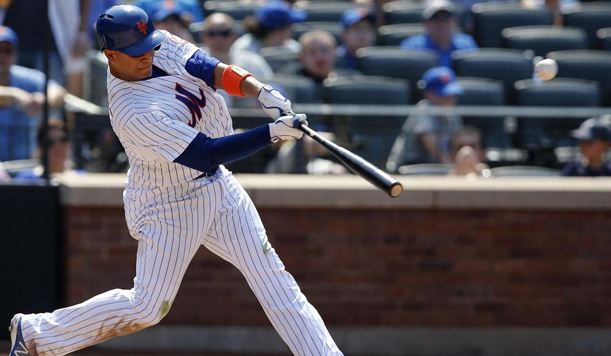 New York Mets Juan Lagares (12) hits a sixth-inning, three-run home run in a baseball game against the Atlanta Braves in New York, Sunday, June 14, 2015. (AP Photo/Kathy Willens)