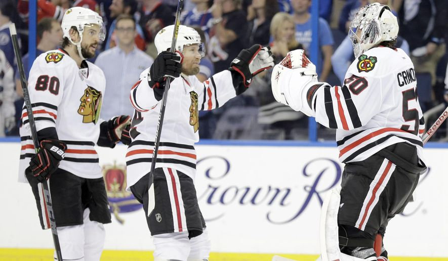 Chicago Blackhawks goalie Corey Crawford (50) is congratulated by center Antoine Vermette (80) and defenseman Kimmo Timonen (44) after the Blackhawks beat the Tampa Bay Lightning 2-1 in Game 5 of the NHL hockey Stanley Cup Final, Saturday, June 13, 2015, in Tampa, Fla. (AP Photo/Chris O'Meara)