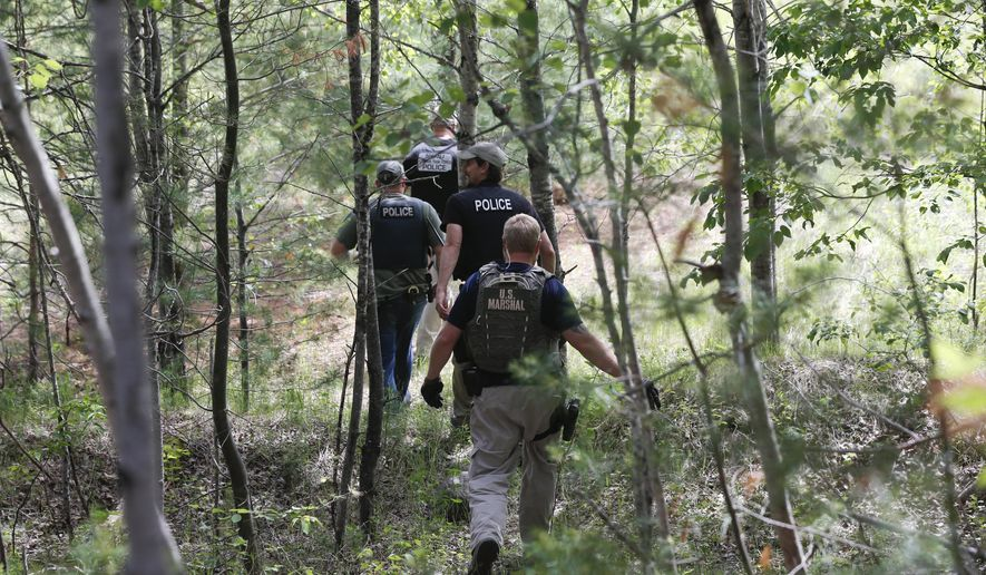 Law enforcement officers walk into the woods behind a residence while searching for escaped prisoners David Sweat and Richard Matt on Sunday, June 14, 2015, in Cadyville, N.Y. Law enforcement personnel are in the ninth day of searching for Sweat and Matt, two killers who used power tools to cut their way out of Clinton Correctional Facility in Dannemora in northern New York. (AP Photo/Mike Groll)