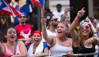 Spectators wave flags during the annual Puerto Rican Day Parade as it makes its way up New York's Fifth Avenue, Sunday,  June 14, 2015. Thousands of people turned out for the parade led by the island's governor. (AP Photo/Kevin Hagen)