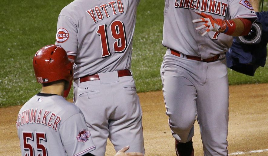 Cincinnati Reds' Eugenio Suarez, right, celebrates with Joey Votto (19) and Skip Schumaker (55) after hitting a two-run home run against the Chicago Cubs during the sixth inning of a baseball game Saturday, June 13, 2015, in Chicago. (AP Photo/Nam Y. Huh)