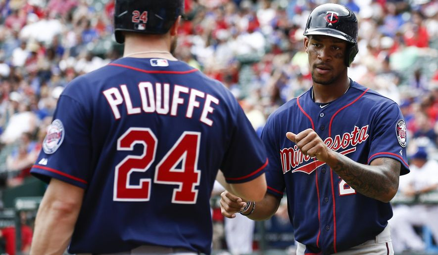 Minnesota Twins' Byron Buxton, right, is congratulated by Trevor Plouffe (24) after scoring the go-ahead run on a double by Eddie Rosario against the Texas Rangers during the ninth inning of a baseball game, Sunday, June 14, 2015, in Arlington, Texas. The Twins won 4-3. (AP Photo/Jim Cowsert)