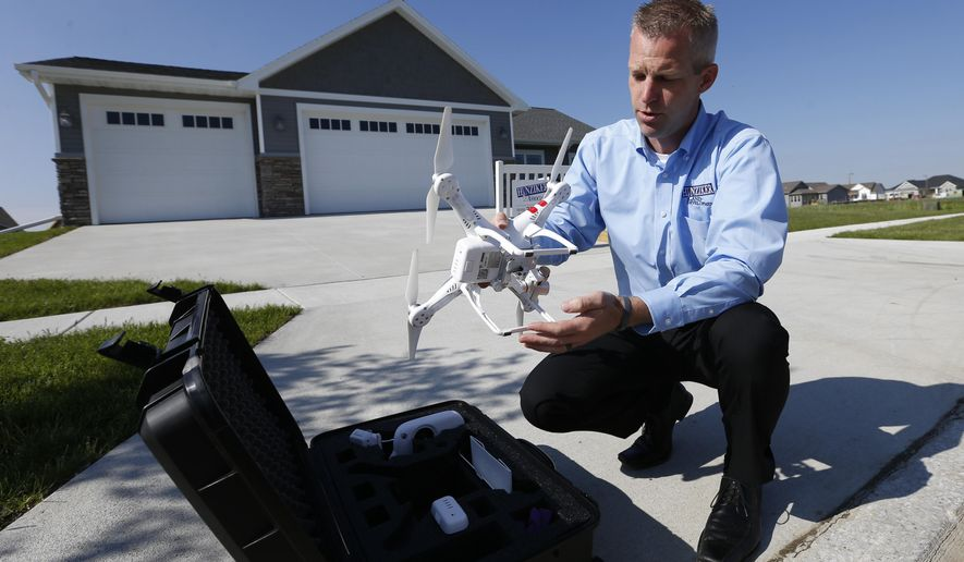 Justin Dodge, development coordinator with Hunziker Land Development unpacks his company's drone device Monday, June, 1, 2015, before taking it for a flight around one of their properties in Ames, Iowa.  Real estate, agriculture, land surveying, photography, research, safety inspections and general hobbyists are all among the initial ventures taking advantage of commercial drones, the same industries that experts predicted would be eager to benefit from their use. (Michael Zamora/The Des Moines Register via AP)  MAGS OUT, TV OUT, NO SALES, MANDATORY CREDIT