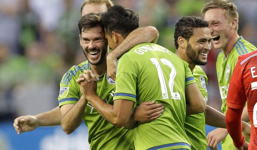 Seattle Sounders' Leo Gonzalez (12) is congratulated by teammates, including Brad Evans, left, after Gonzalez scored a goal against FC Dallas during the second half of an MLS soccer match, Saturday, June 13, 2015, in Seattle. The Sounders won 3-0. (AP Photo/Ted S. Warren)