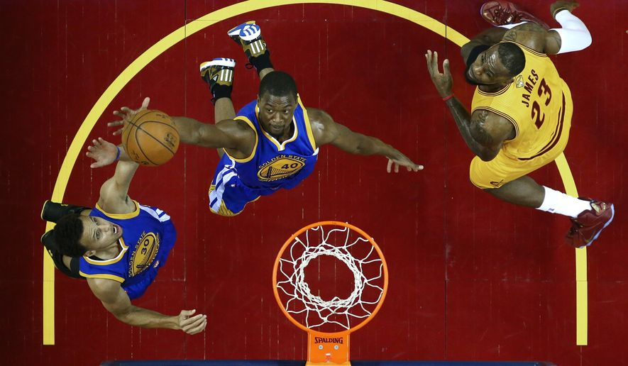 Golden State Warriors guard Stephen Curry (30), left, and teammate forward Harrison Barnes (40) go for a rebound over Cleveland Cavaliers forward LeBron James (23) during the first half of Game 4 of basketball's NBA Finals in Cleveland, Thursday, June 11, 2015. (Ronald Martinez/Pool Photo via AP)