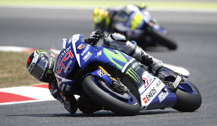 Moto GP rider Jorge Lorenzo of Spain, steers his motorcycle as he is followed by Valentino Rossi of Italy, during the Catalunya Motorcycle Grand Prix at the Barcelona Catalunya racetrack in Montmelo, near Barcelona, Spain, on Sunday, June 14, 2015. (AP Photo/Manu Fernandez)