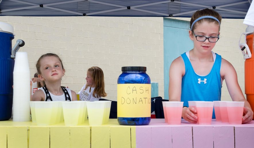 CORRECTS SPELLING OF FIRST NAME TO JADYN INSTEAD OF JAYDN - In a Sunday, June 14, 2015 photo, Jadyn Horst, 10, right and Kalyn Horst, 6, center, operate their lemonade stand in the parking lot of Black Elk Elementary School in Omaha, Neb. Around $3,500 was raised this weekend. The money from the sisters' lemonade stand and sales by food vendors at the Sunday fundraiser went toward the Wounded Warriors Family Support and Moving Veterans Forward organizations. (Kent Sievers/Omaha World-Herald via AP)