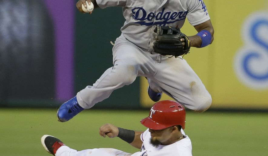 Los Angeles Dodgers shortstop Jimmy Rollins (11) jumps over a sliding Texas Rangers Rougned Odor at second base breaking up the double play attempt during the fifth inning of a baseball game in Arlington, Texas, Monday, June 15, 2015. Rangers Leonys Martin was safe at first.  (AP Photo/LM Otero)