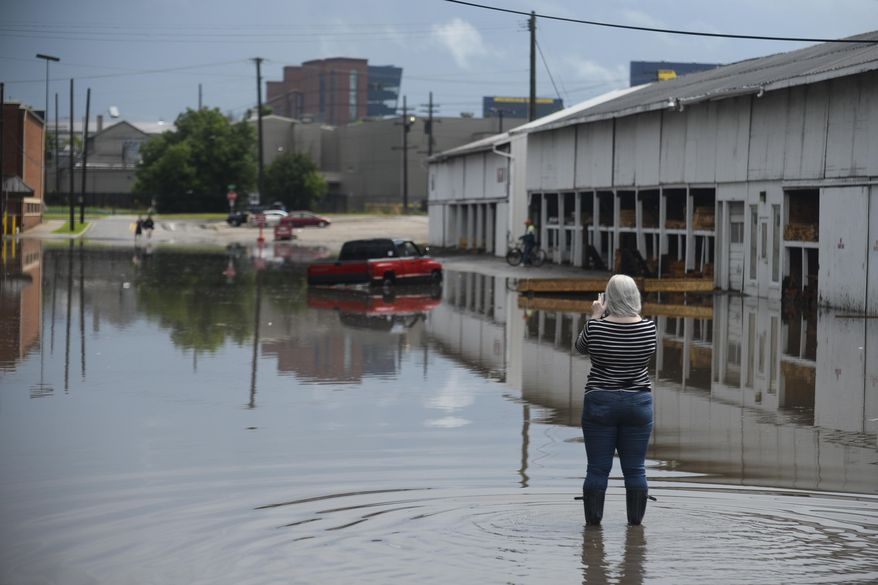 In this Sunday, June 14, 2015 photo, a woman takes photographs of floodwaters near Fingerle Lumber Co. in Ann Arbor, Mich. Flood advisories are in effect along a number of waterways in Michigan's Lower Peninsula following heavy weekend rains and a forecast calling for more storms. (Alex McDougall/The Ann Arbor News via AP) LOCAL TELEVISION OUT; LOCAL INTERNET OUT