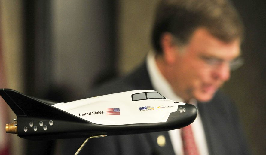 A model of the Sierra Nevada Dream Chaser sits on the podium as Mayor Tommy Battle speaks as Huntsville leaders announce that Huntsville will study the feasibility of landing the Sierra Nevada Corporation's Dream Chaser spacecraft at Huntsville International Airport, during a press conference at the Chamber of Commerce Monday June 15, 2015. The study will take about six months, and landings could begin as early as 2018 when Dream Chaser is expected to begin space flight.  (Eric Schultz/The Huntsville Times via AP)