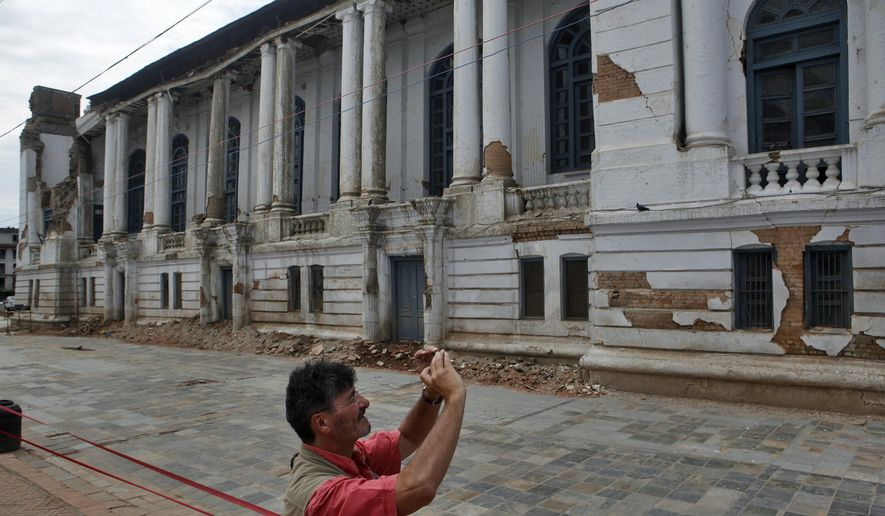 Tourist photographs a damaged building near Basantapur Durbar Square in Kathmandu, Nepal, Monday, June 15, 2015. Nepal on Monday reopened most of the cultural heritage sites that were damaged in a pair of devastating earthquakes, hoping to lure back foreign tourists. (AP Photo/Niranjan Shrestha)