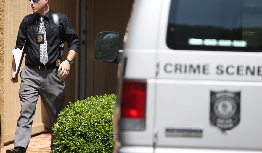 A DeKalb County Police investigator leaves the apartment where a 10-year-old boy was shot in the head on Monday, June 15, 2015 in Lithonia, Ga. Police said that the shooting, which left the boy in critical condition, was reported as an accidental shooting. Two relatives, age 7 and 24 were home at the time of the shooting. (Ben Gray/The Atlanta Journal-Constitution via AP) MARIETTA DAILY OUT, GWINNETT DAILY POST OUT, LOCAL TV OUT (WXIA, WGCL, FOX 5)