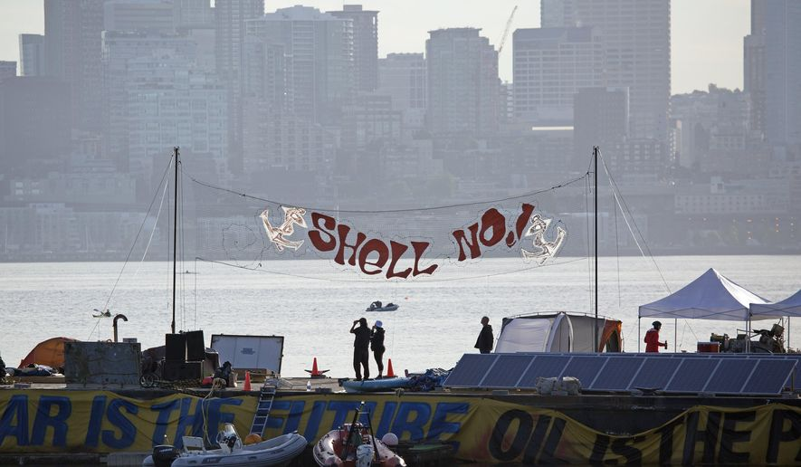 Protesters stand on a barge as they watch the Shell oil rig, the  Polar Pioneer, depart from Terminal 5 early in the morning on Monday, June 15, 2015. The U.S. Coast Guard says it has detained several protesters in kayaks Monday who tried to block Royal Dutch Shell's drill rig as it leaves Seattle on its way to explore for oil in the Arctic Ocean. (Sy Bean/The Seattle Times via AP)  OUTS: SEATTLE OUT, USA TODAY OUT, MAGAZINES OUT, TELEVISION OUT, SALES OUT. MANDATORY CREDIT TO: SY BEAN / THE SEATTLE TIMES.