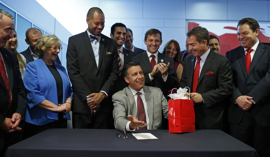 File - In this June 11, 2015, file photo, Nevada Gov. Brian Sandoval, center, reacts after signing SB 514 into law at the University of Nevada, Las Vegas in Las Vegas. The Republican governor wrapped up his work signing and vetoing bills Friday, less than two weeks after lawmakers finished their 120-day session. Sandoval vetoed a career-low seven bills that passed the Republican-controlled Legislature. (AP Photo/John Locher, File)