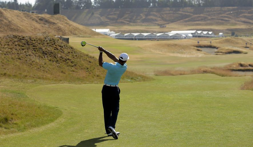 Tiger Woods watches his tee shot on the 18th hole during a practice round for the U.S. Open golf tournament at Chambers Bay, Monday, June 15, 2015, in University Place, Wash. (AP Photo/Ted S. Warren)