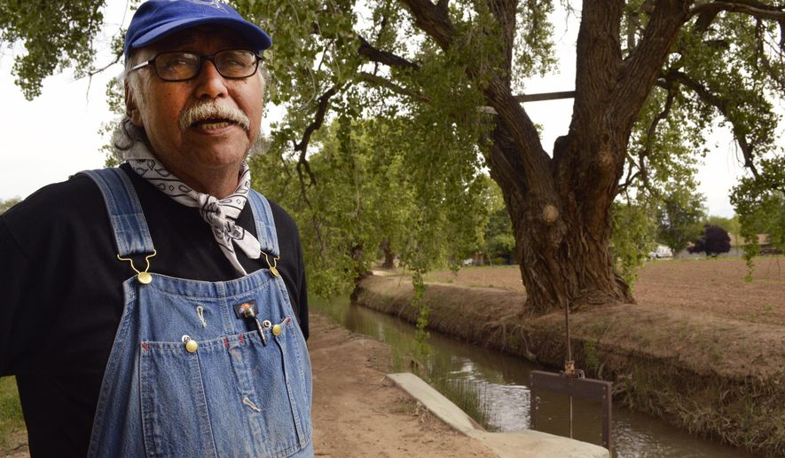 This May, 14, 2015 photo, Santiago Maestas, 67, stands by a community irrigation canal near his property and talks about the limited water resources for the canal in Albuquerque's South Valley. Commissioners in Bernalillo County, New Mexico's most populous county, are scheduled Tuesday, June 16, 2015 to make a decision on a planned community west of Albuquerque called Santolina that developers say could be home to 90,000 people. But the plan is drawing opposition from some nearby residents over water concerns. (AP Photo/Russell Contreras)