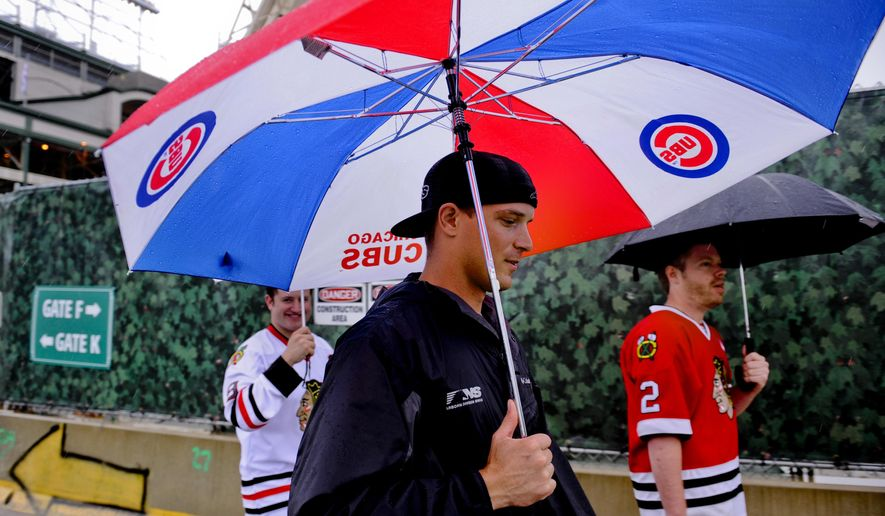 Fans leave Wrigley Field after rain postponed a baseball game between the Chicago Cubs and the Cleveland Indians, Monday, June 15, 2015, in Chicago. (AP Photo/Matt Marton)