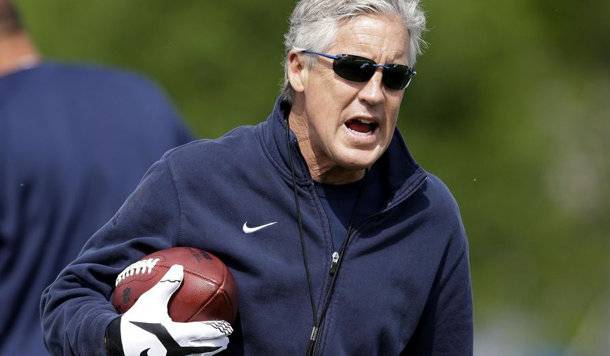 FILE - In this May 10, 2015, file photo, Seattle Seahawks head coach Pete Carroll walks on the field during an NFL football rookie minicamp in Renton, Wash. Last offseason, the Seahawks went a little too hard in practice. And they're about to pay for it during the team's mandatory minicamp this week with the league taking away two practices. (AP Photo/Elaine Thompson, File)