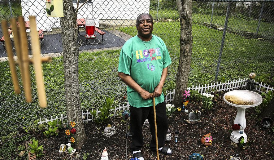 In this May 12, 2015 photo, Michael Pinnick stands in his serenity garden at his home in Joliet, Ill. Pinnick, a former drug addict, is suffering from lymphoma and lung cancer. When Pinnick was first treated in 2014 for lung cancer and lymphoma, he rejoiced when other patients graduated from treatments. He waited for his day to arrive. But now that the cancer in his lungs and lymph nodes has spread to his bones, brain and liver, Pinnick is realizing that day might never arrive. (Lathan Goumas/The Herald-News via AP)  CHICAGO TRIBUNE OUT, MANDATORY CREDIT