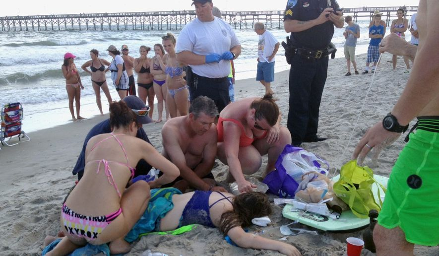 Emergency responders assist a teenage girl at the scene of a shark attack in Oak Island, North Carolina on Sunday. Hours after the teenage girl suffered severe injuries in a shark attack Sunday a teenage boy was also severely injured in an attack by the same shark. Oak Island's beaches were open on Monday. (The Pilot, Southern Pines, N.C. via Associated Press)