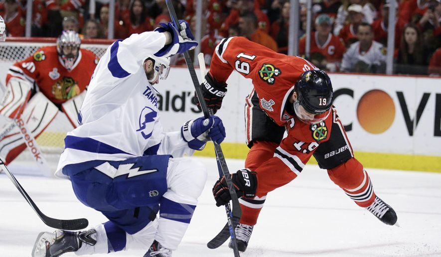 Chicago Blackhawks' Jonathan Toews, right, reaches for a puck after a face-off along side Tampa Bay Lightning's Cedric Paquette during the first period in Game 6 of the NHL hockey Stanley Cup Final series on Monday, June 15, 2015, in Chicago. (AP Photo/Nam Y. Huh)