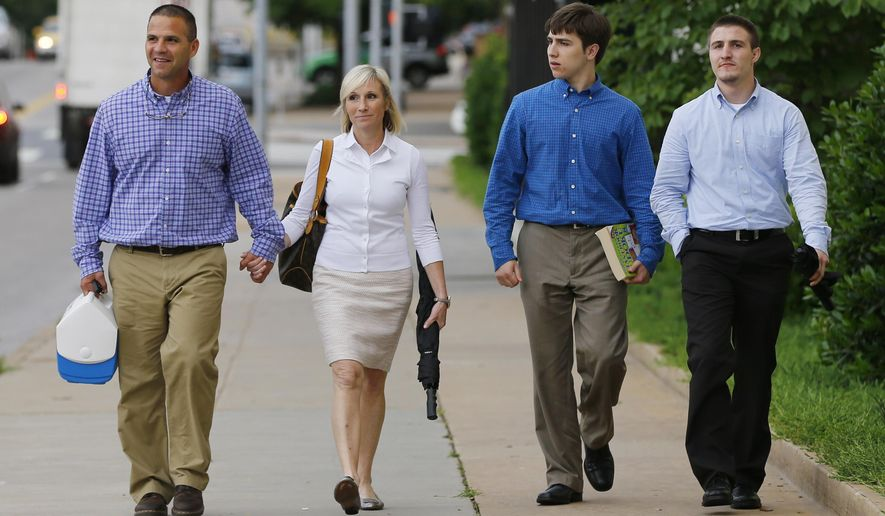Kyle Durham, left, and Melissa Durham, second from left, hold hands as they leave the Federal Courthouse in Oklahoma City, following another day of testimony in the federal trial of their son, Matthew Lane Durham, Monday, June 15, 2015. At right are their other two sons, Josh Durham, right, and Zac Durham, second from right. Matthew Lane Durham is accused of 17 counts of sexual misconduct with children in Nairobi, Kenya.  (AP Photo/Sue Ogrocki)