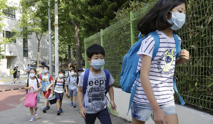 South Korean elementary school students wearing masks as a precaution against the Middle East Respiratory Syndrome virus go to school as their school reopened after it was temporarily closed in Seoul, South Korea Monday, June 15, 2015. The outbreak of Middle East respiratory syndrome has caused panic in South Korea. (AP Photo/Ahn Young-joon)