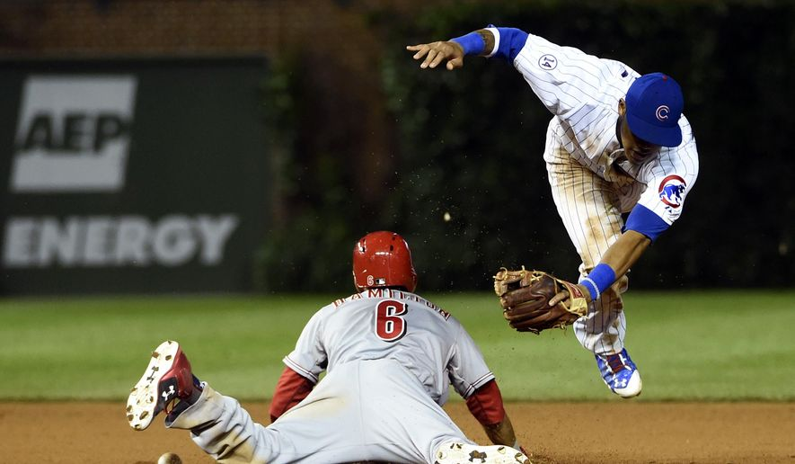 Cincinnati Reds' Billy Hamilton (6) steals second base as Chicago Cubs second baseman Addison Russell (22) tries to tag him during the 10th inning of a baseball game Sunday, June 14, 2015, in Chicago. (AP Photo/David Banks)
