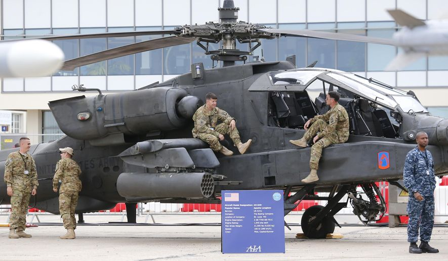 U.S army personnel stand on the Boeing Helicopter AH-64D Apache Longbow at the Paris Air Show in le Bourget, east of Paris, on the eve of its opening, Sunday, June 14, 2015. The Paris Air Show will take place at the Bourget airport, north of Paris, from June 15 to June 25. (AP Photo/Jacques Brinon)